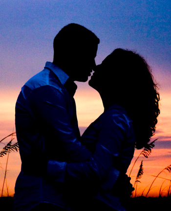 A kissing couple enjoys the ease of a great relationship