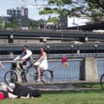 A couple riding a tandem bike in the waterfront park with balloons trailing out behind them