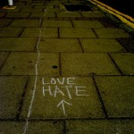 """""""love hate"""" and an arrow (this way!) written on a sidewalk"""