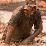 a guy slogs through thigh-deep mud