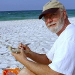 A man works on a small sculpture on the beach