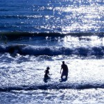 A child and an adult play in the ocean
