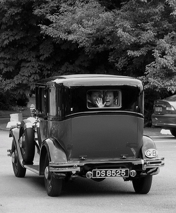 happy couple waves goodbye out the back window of an old car